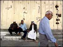 Iraqi men chat while sitting outside closed shops in Baghdad