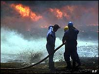 Iraqi workers fight an apparently accidental oil fire near Faw in March 2004