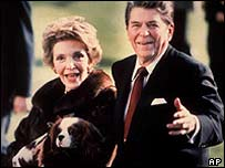 Nancy Reagan holds the family's King Charles spaniel Rex, as she and President Ronald Reagan stroll along the White House South Lawn, December 1986