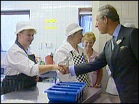 Prince Charles shaking hands with dinner ladies