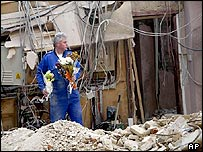 British forensic officer clears condolence flowers from the rubble of the bombed consulate in Istanbul