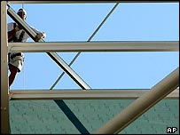 Workers walk on top of the steel-and-glass roof of the Olympic stadium