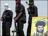 Armed supporters of Moqtada Sadr, standing near a portrait of their leader