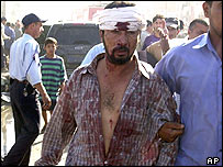 An injured man is led from the scene of a car bomb in central Baghdad on 14 June
