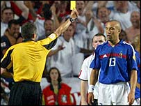 France defender Mikael Silvestre escapes with a yellow card after bringing down Wayne Rooney