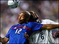 Thierry Henry and Sol Campbell go for the ball
