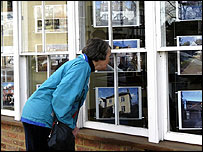Someone looking in an estate agent's window