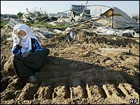 A Palestinian woman sits in bulldozer tracks after farmland was cleared in Gaza