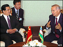Uzbek President Islam Karimov (R) talks to Chinese President Hu Jintao at the airport in Tashkent 14 June 2004.