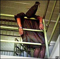 Hooded prisoner handcuffed to an Abu Ghraib walkway (courtesy Washington Post)