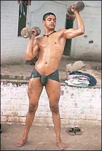 A pehlwan trainee exercising with weights