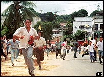 People in Ambon run down a street after violence between Christian and Muslim groups, May 1999