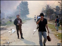 Muslim gang members carry makeshift rifles as Christian homes burn in sectarian violence-wracked Poso, December 2001