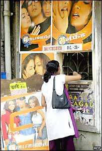 An Indian woman buys tickets at a cinema as she stands beside advertising for one of Bollywood's latest films 'Girlfriend' in Calcutta