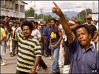 A mob of Papuan independence supporters shout at approaching Indonesian security forces, Nov 2001