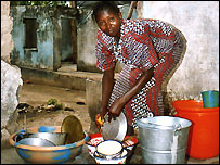 Woman washing dishes in Sierra Leone