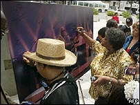 Mourners queue to sign a picture of late musican Ray Charles