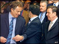 Tony Blair walks past Gerhard Schroeder