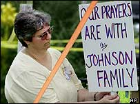 Joanne Petro puts up a sign in support of the family of Paul Johnson