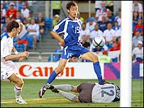 Zisis Vryzas lifts the ball into the net to score the Greece goal which ensured their last eight place