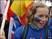 Child carries collection of European flags