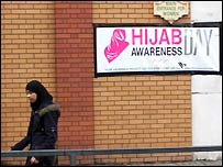 Woman walks by sign that reads 'Hijab Awareness Day'