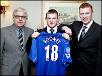 Rooney (centre) celebrates signing his first professional contract at Everton