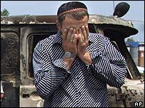 Ingush man weeps next to a burned out jeep in Nazran