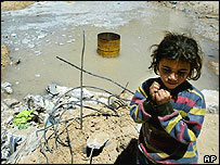 Child standing by pool of raw sewage, AP