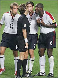 Gary Neville (centre), his brother Phil and Sol Campbell dispute referee Urs Meier disallowing the altter's late goal