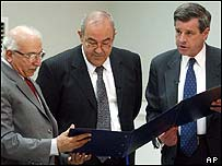 Paul Bremer (right) hands power to Iraqi Prime Minister Allawi (centre) and Chief Justice Mahmoudi (left)
