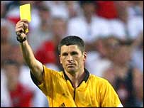 Markus Merk shows a yellow card to Robert Pires of France