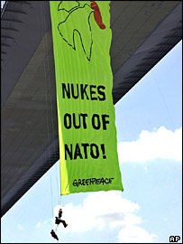 Greenpeace activists unfurl a banner from a bridge
