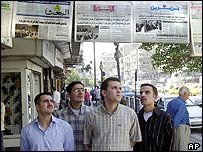 Men read newspapers in Damascus
