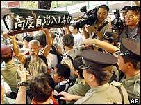 Activists push past police as they carry a mock coffin with the Chinese characters: 'A high degree of autonomy has already  been buried' 1/07/04