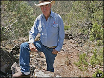 Former owner Waldo Wilcox stands in the remains of a pit house