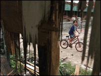 Young Dayak child near a damaged house in Kalimantan