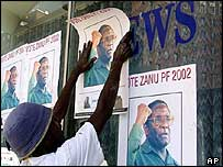 Man putting Robert Mugabe posters on Daily News office