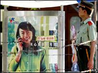 Китайский милиционер у рекламы мобильного телефона