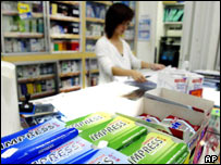 Singaporean pharmacist works behind her counter where Impress chewing gum is for sale