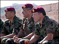King Abdullah watches a military exercise in the Jordanian desert