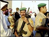 Policeman at a Bahrain fair rubs shoulders with a man with a falcon