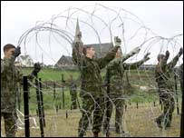 Soldiers put a razor wire barrier near the church