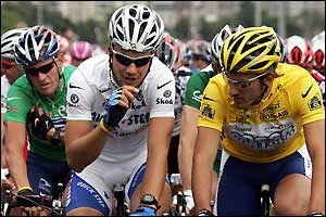 Lance Armstrong looks on behind Cancellara