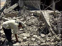 A Falluja resident picks through the rubble of a house following a US air strike in June