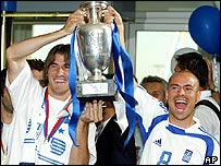 Greece players Giourkas Seitaridis and Stelios Giannakopoulos hold aloft the Euro 2004 trophy as the team arrive at Athens airport