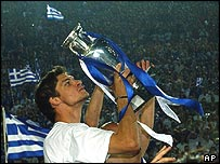 Greece striker Angelos Charisteas shows off the Euro 2004 trophy to thousands of fans gathered in the old Olympic stadium in Athens