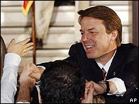 John Edwards saluda en las escaleras del capitolio del estado de Atlanta.