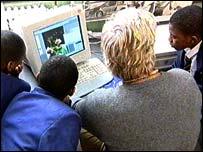 children and teacher at computer