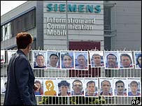 Siemens workers' photos pinned to a fence to protest proposed job cuts